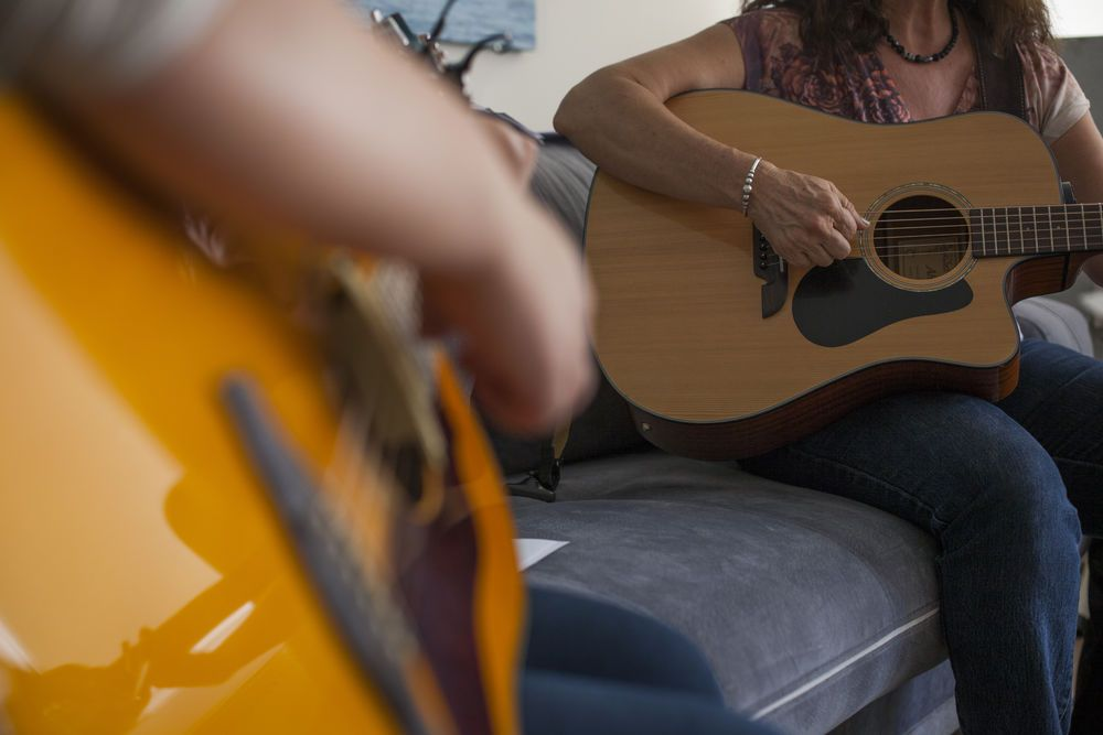Turkey: Short-term OMer Sandy (right) practices guitar with a member of the TACO team. More Info