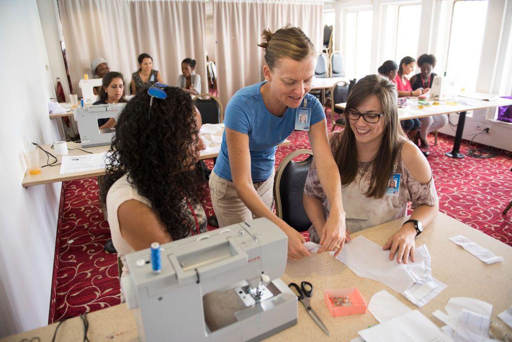 Haiti: Port-au-Prince, Haiti :: Catherine De Freitas (New Zealand) and Amy Strickland (USA) teach a woman how to sew a school uniform. More Info