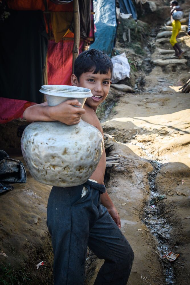 Bangladesh: A young boy pauses for the camera on his trip home with a jug of water. Photo by Garrett N. More Info