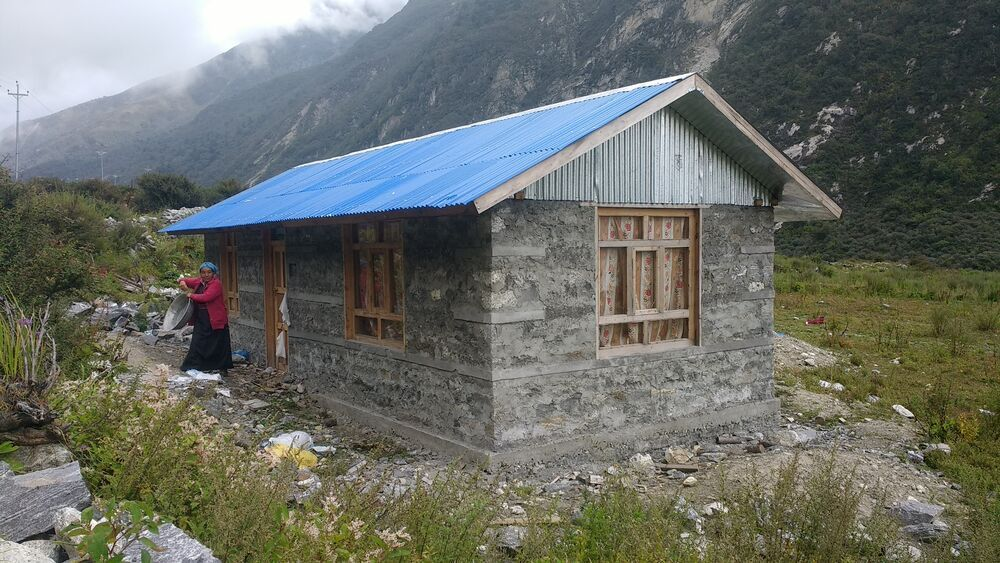 Nepal: Langtang villager enjoys her new house after it was destroyed by the 2015 earthquake in Nepal. This is one of the six model houses being built by OM Nepal. More Info