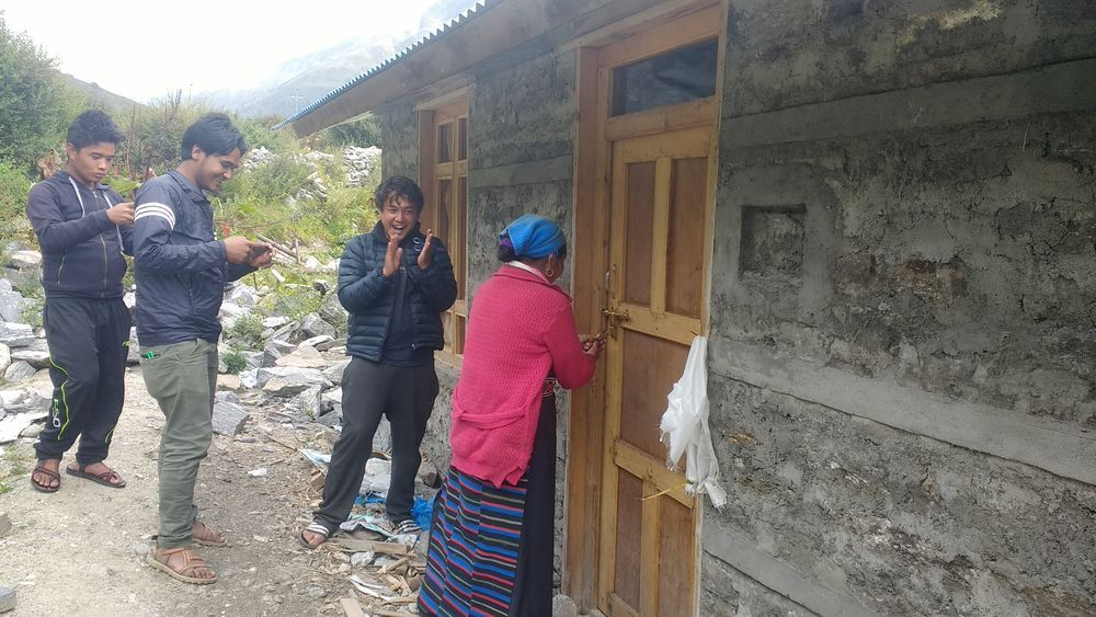 Langtang villager is being applauded as she opens the door to her new home after her old home was destroyed by the 2015 earthquake in Nepal. This is one of the 6 model houses being built by OM Nepal.