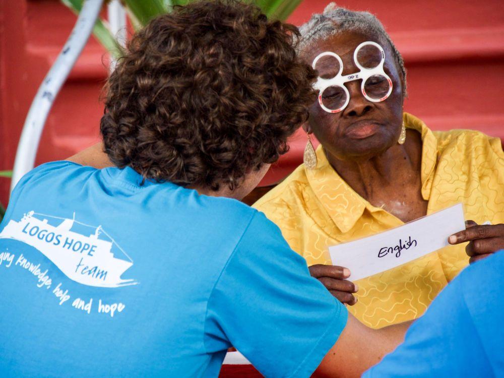 Grenada: Saint George, Grenada :: Micha Roggensinger (Switzerland) tests an elderly woman for new reading glasses. More Info