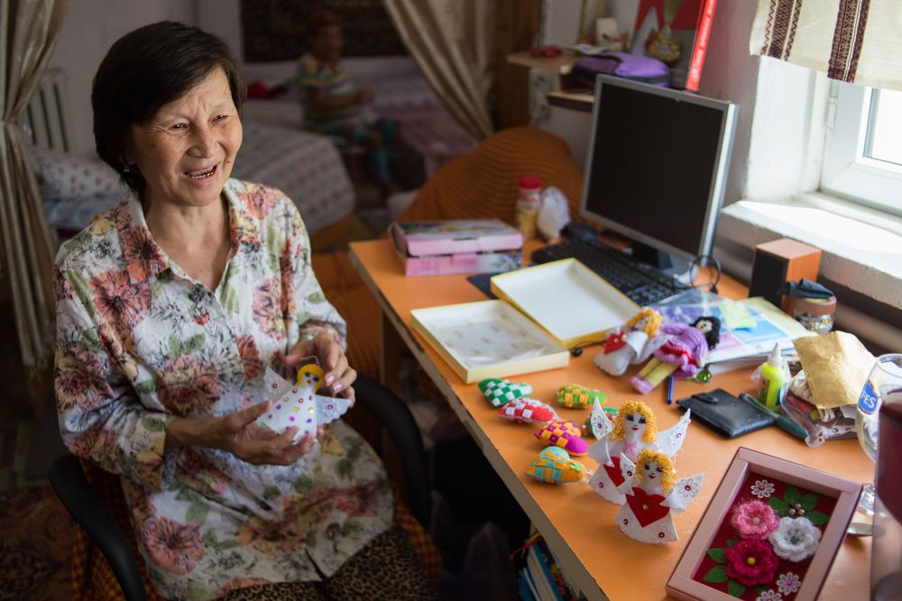 A Central Asian woman displays the handicrafts she makes while living in a womens shelter.