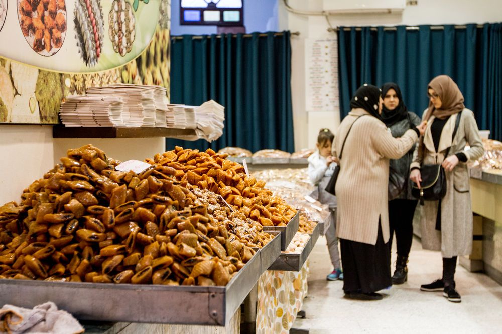 North Africa: Women discuss what to buy inside a sweets shop. More Info