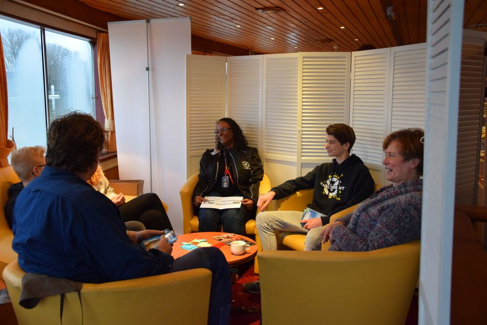 Community member, Sandra Jagroep (Netherlands), debriefing a group after they had gone through The Agency experience on board.