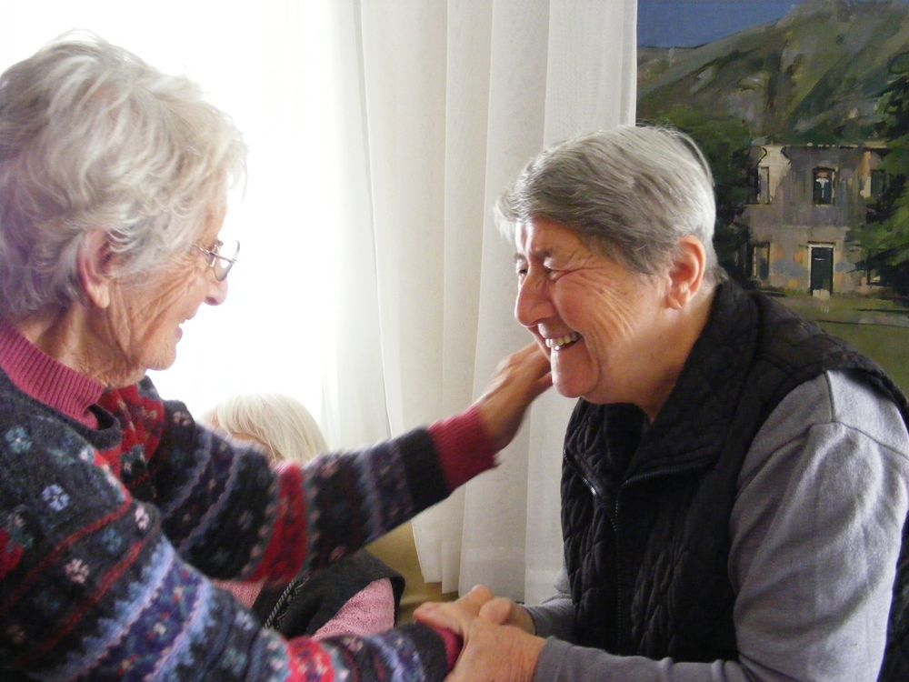 Warm handshakes unite an English visitor and a resident at a Montenegrin care home.