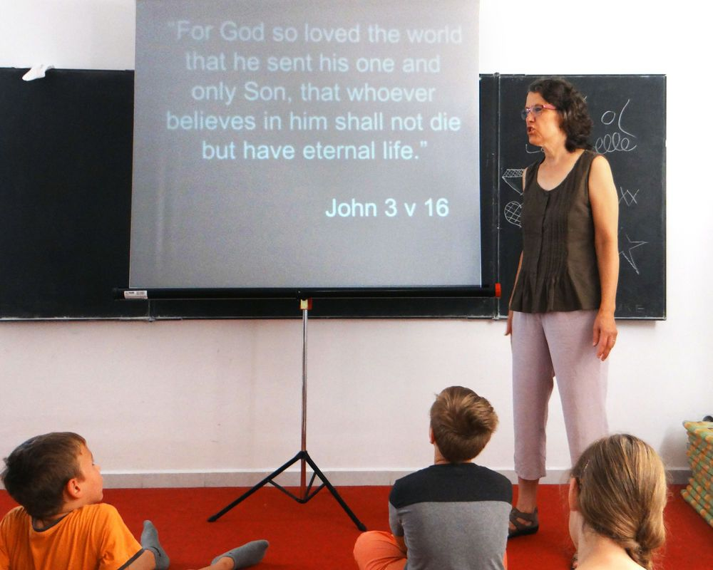 Hungary: OMer Ilona shares a Bible verse with children during an English camp outreach in Hungary in 2017. More Info