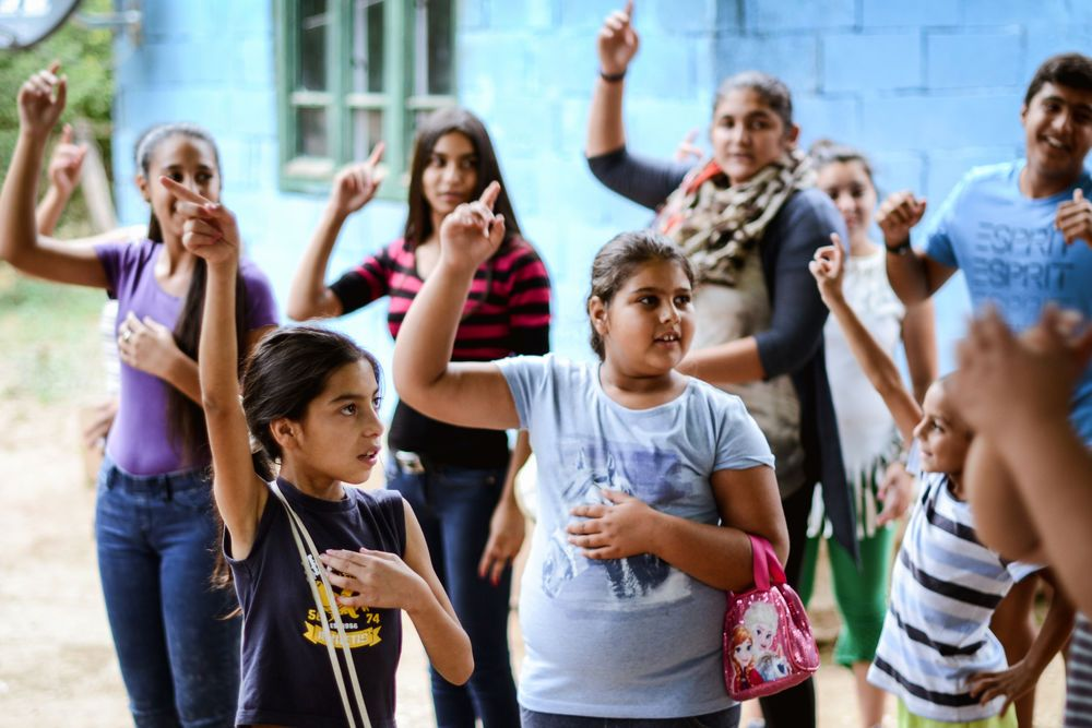 International: Children and teenagers singing in a village in Serbia. OM EAST produces materials needed for their partners to run children's clubs among Roma communities. Do not post to Facebook More Info