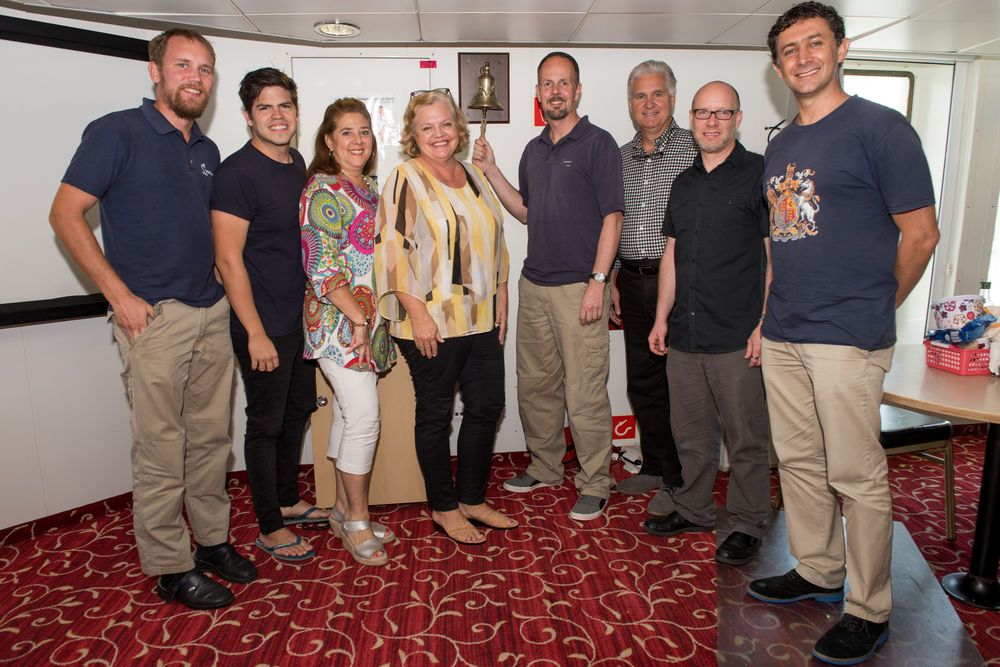 Colombia: Cartagena, Colombia :: Endre Bjorå (Norway), Ruben Muñoz (Mexico), Marta Ardila (Colombia), Kim Grebe (USA), Dirk Colenbrander (Netherlands), Randy Grebe (USA), Jon Crowe (USA) and Carlos Montañez (Colombia) stand next to the bell in the dining room. More Info