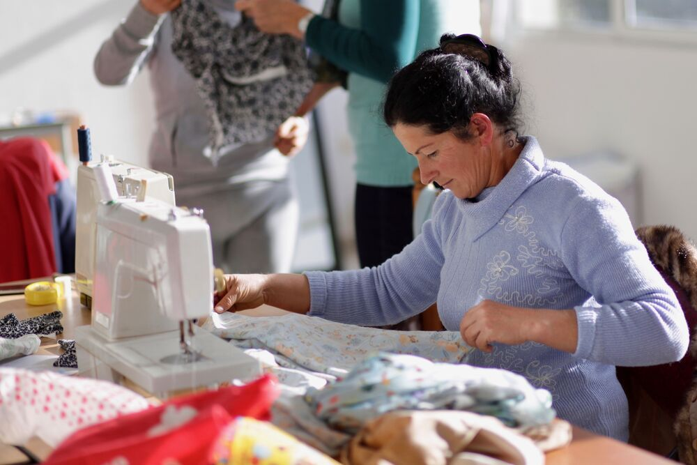 An Albanian woman learns sewing skills at OM Albanias evangelistic sewing course for local  women where they not only learn to sew, but also study the Bible and hear the gospel.