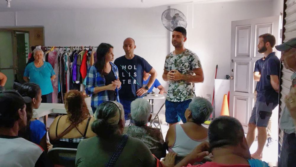 Mexico: Veracruz, Mexico :: Stepan Vardanian (Armenia, centre) speaks to homeless people visiting a clothes bank run by a local church, as other crewmembers look on. More Info