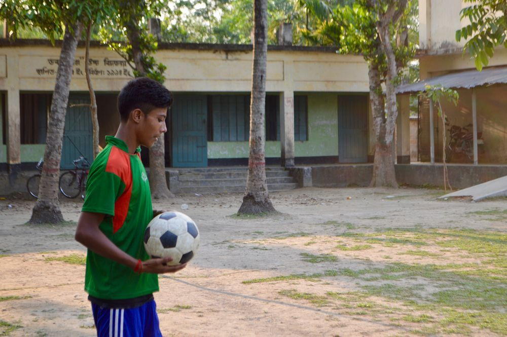 A student joins the football game with his teammates in Bangladesh, part of the village outreach using sports to build relationships and teach biblical values.