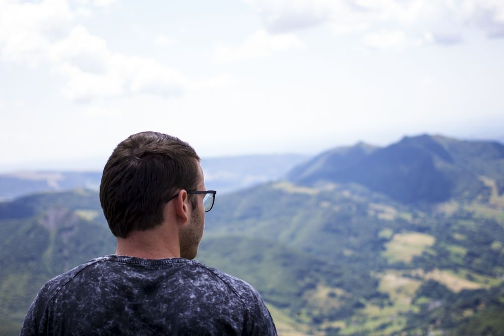 Norwegian young man sits and stares at Gods creation on top of Puy Mary in the Cantal Region of France.