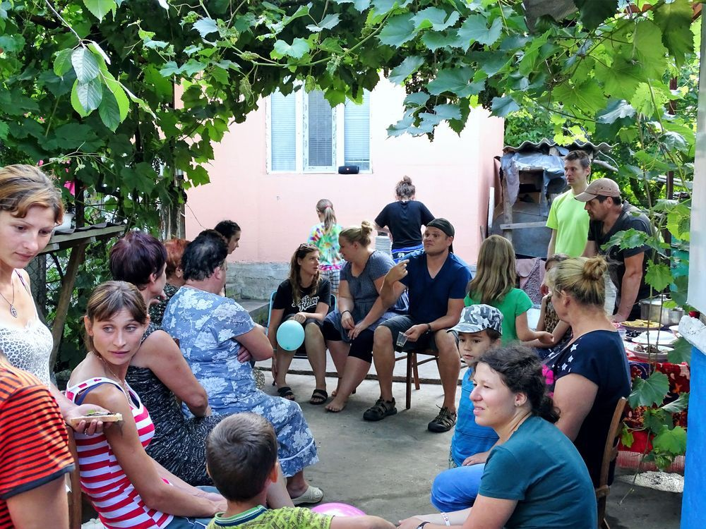 """Moldova: Members of an outreach team continue discussing with local villagers after leading an evangelistic event at the home of the only believer in the community, whom God had led them to by a """"chance"""" meeting. More Info"""