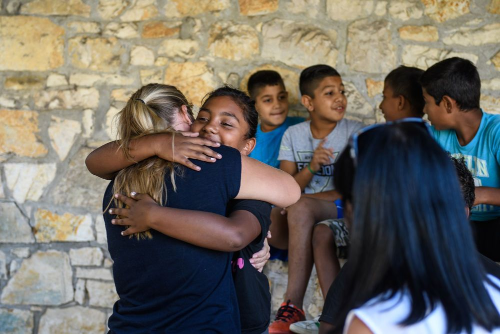 Women, as part of mercy ministry, pass out backpacks filled with school supplies and clothes to Roma children.  Photo by Garrett N