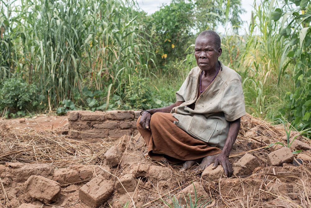 """Malawi: Esther sits in the rubble where her house once stood in a village in Malawi. Esther, a widow, was alone in her home when it started collapsing under the strong rains of Cyclone Idai. One wall crumbled while she was still inside and the rest fell once she was out.  """"I was very scared. That's when my daughter came and rescued me,"""" said Esther who is now staying in her daughter's house 50 feet away. More Info"""