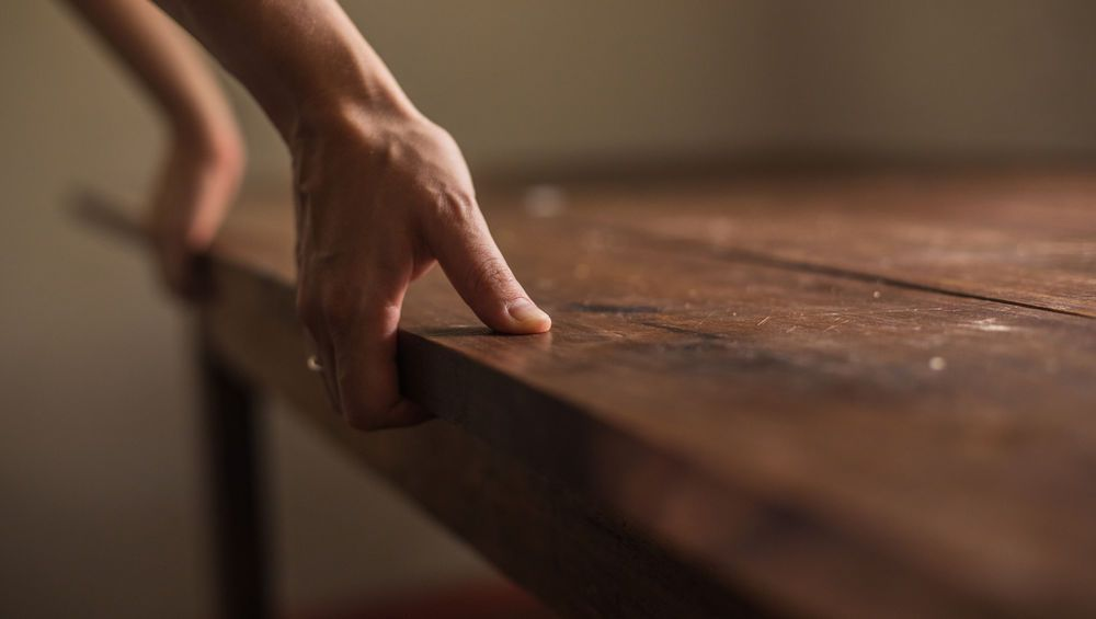 Hands grasping the edge of a table.