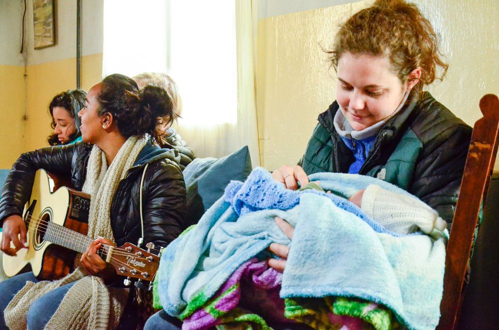 Mar del Plata, Argentina :: Joan Lisa Shramm (Germany) holds a baby during worship in a Christian rehabilitation center.