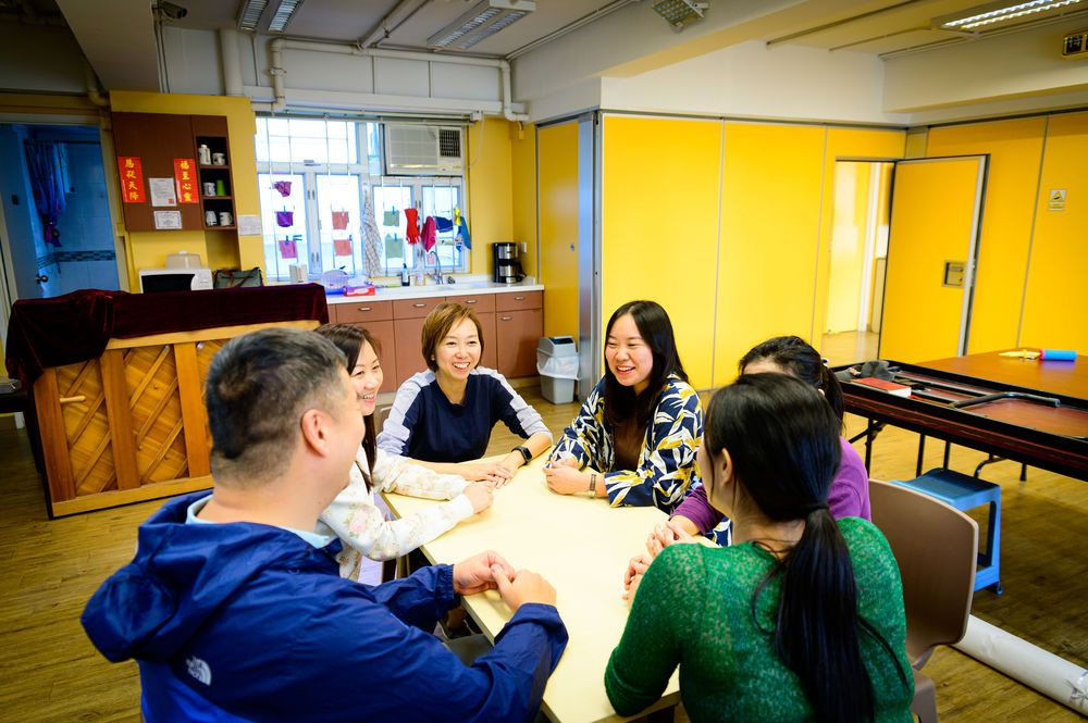 Hong Kong: Staff workers enjoy fellowship around a table. More Info