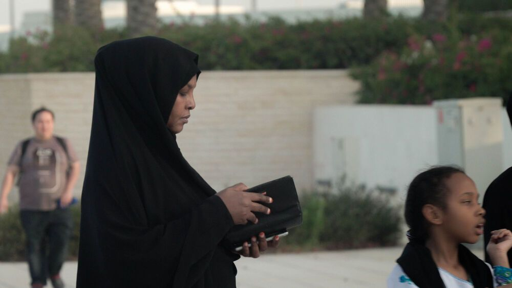 A Muslim woman checks her purse while waiting to enter a mosque. Photo by Jay S.