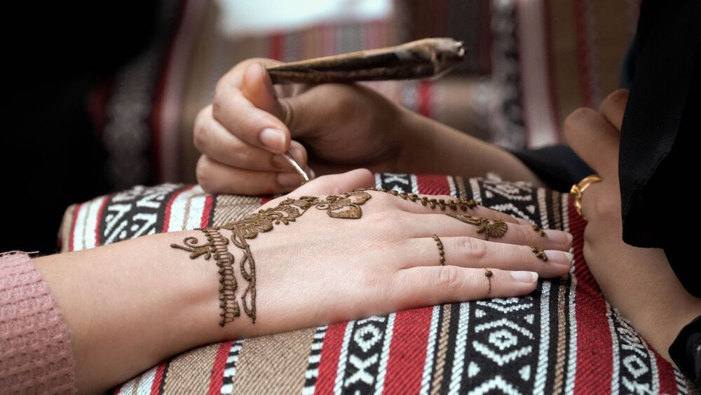 An Arab woman decorates a womans hand with a henna design. Photo by Jay S.