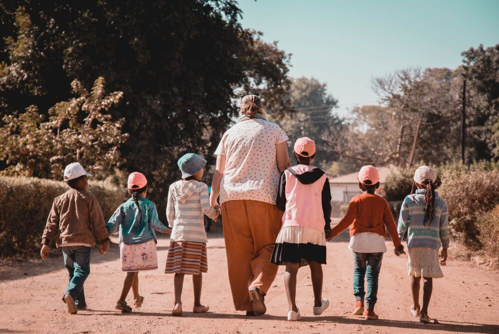 Zambia: Anne Davidson, the coordinator of Mercy House ministry in Kabwe, Zambia walking down the road with children. Photo by Kauya Mali. More Info