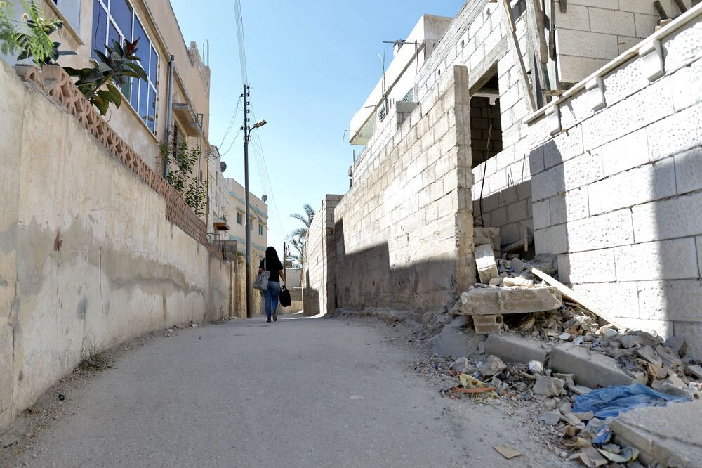 Near East: Sarah walks down a street on her way to a medical home visit. More Info