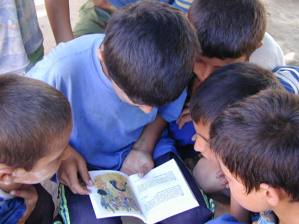 Group of boys eagerly looking at a small booklet
