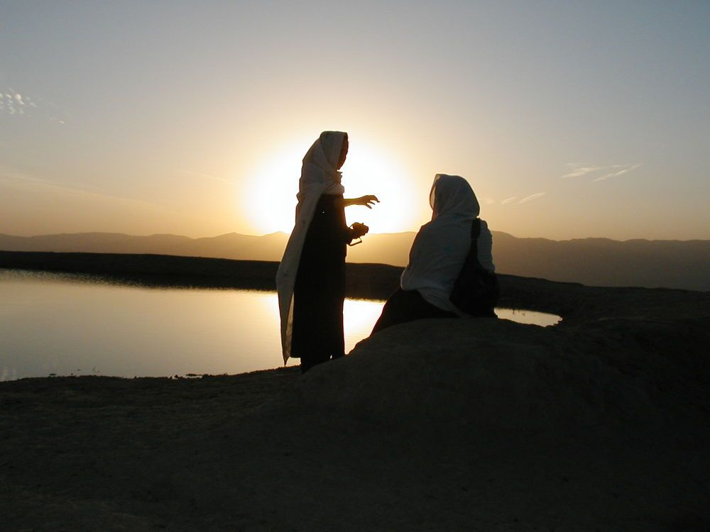 Silhouette of two women by water.