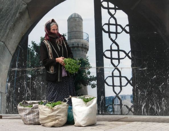 Caucasus: Elderly woman selling vegetables for a living, standing in front of poster More Info