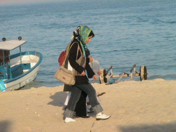 Iran: Two veiled women wearing modern clothes walk by the seaside. More Info