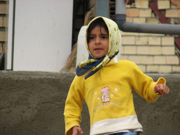 Iran: Girl wearing a yellow fleece sweater More Info