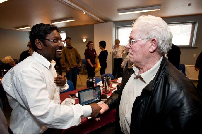 Faroe Is.: Klaksvik, Faroe Islands  ::  Jaison Ebenzer (India) having a conversation with a local man at an Elderly Fellowship. More Info