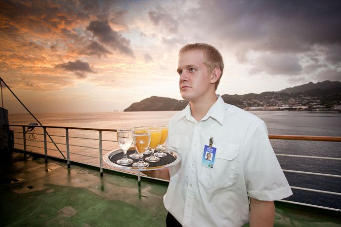Saint Vincent & the Grenadines: Kingstown, St. Vincent  ::  Francois Vosloo (South Africa) serving juice and cold water at a Special Reception on the Boat Deck. More Info