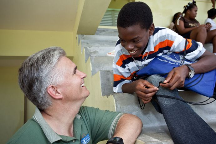 Saint Vincent & the Grenadines: Kingstown, St. Vincent  :: Randy Grebe (USA) speaks with a local boy at an onshore event. More Info