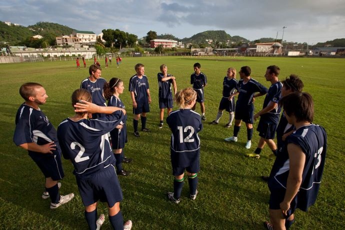 Grenada: St. Georges, Grenada  ::  The team huddling prior to the start of a football match.  The local team can be seen in the distance. More Info