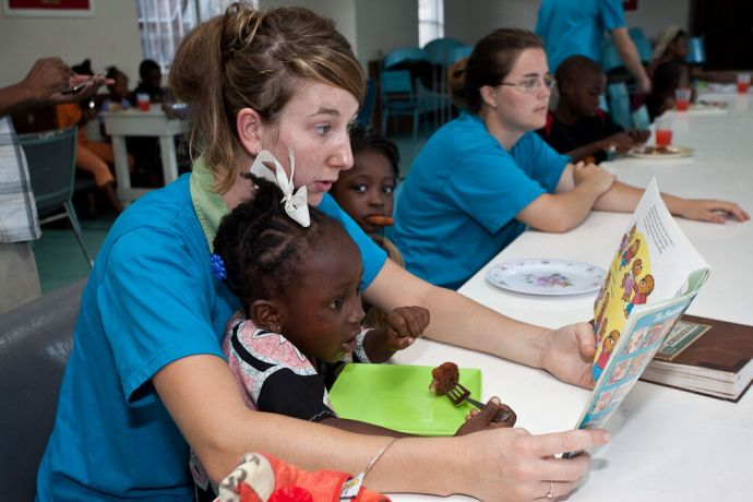 Barbados: Bridgetown, Barbados :: Maddy Brown (UK) reading to one of the kids at the Kids Breakfast Club. More Info