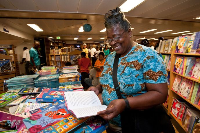 Barbados: Bridgetown, Barbados :: A local woman  looking over the childrens books. More Info