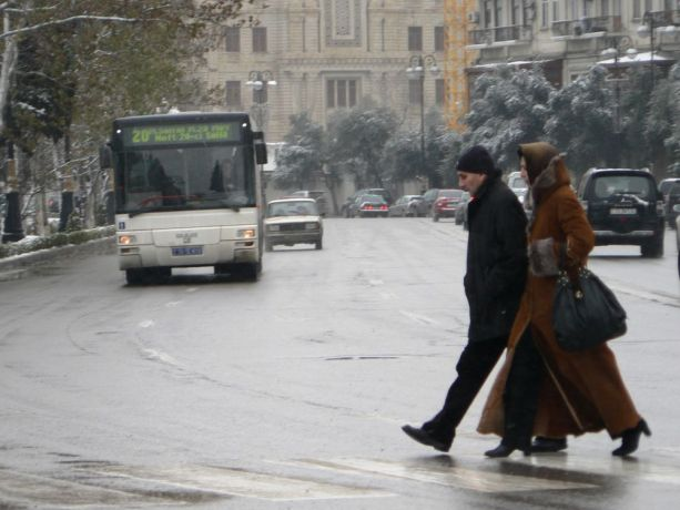Caucasus: A couple dressed in full length winter coats crossing the a city street in Baku More Info
