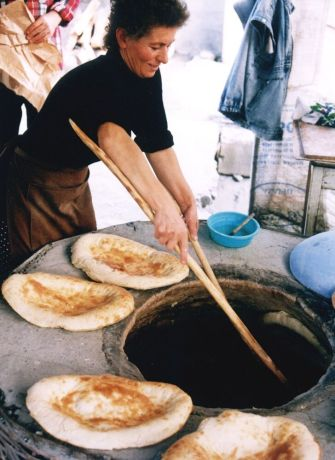 Caucasus: Woman making bread in a tandoor oven More Info