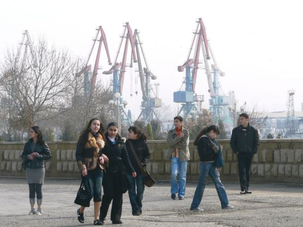 Caucasus: Group of young people with harbour cranes in background More Info