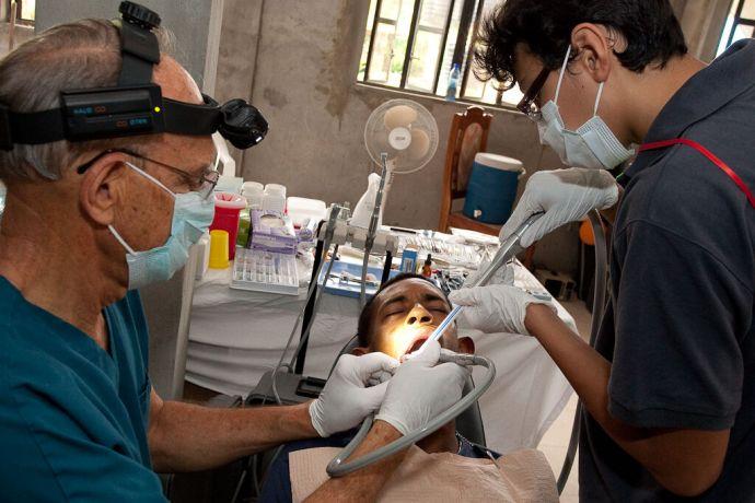 Guyana: Georgetown, Guyana  ::  Dr Al Warren D.D.S. (USA) working on a patient with Saurzhan Yakupov (Kazakhstan)  assisting at the Parika YWAM Base. More Info