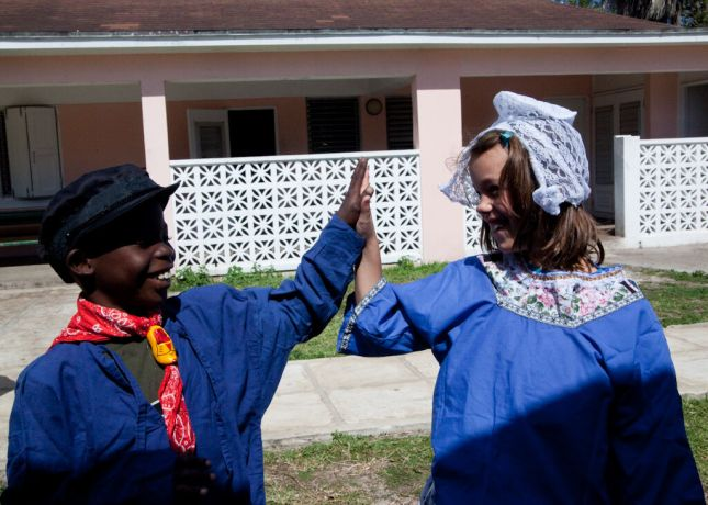 Bahamas: Nassau, Bahamas :: Jennifer Zandbergen (Netherlands) gives a high five to a local child in an orphanage, both dressed in the Netherlands national costume. More Info