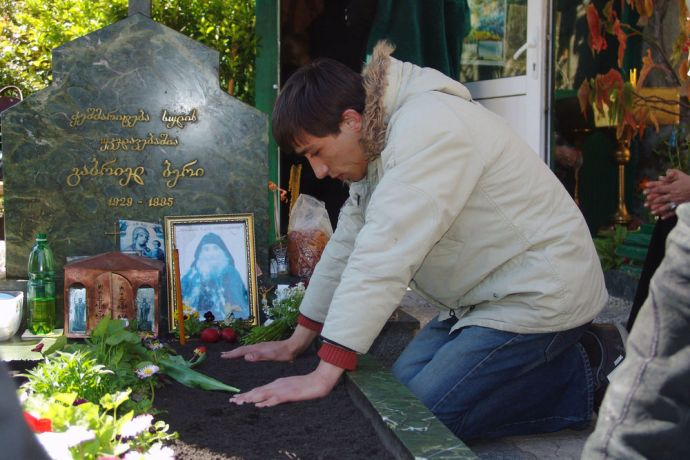Caucasus: A Georgian Man praying for dead relatives according to Orthodox custom. More Info