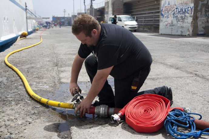 Cape Verde: Mindelo, Cape Verde :: 3rd Engineer Josef Jacobsen (Faroe Islands) assists with the water supply during the stopover in Mindelo. More Info