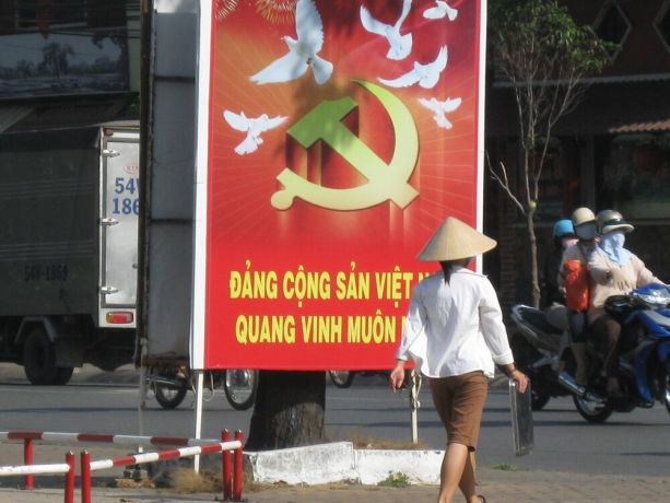 Vietnam: Woman in cone hat walking in front of Communist poster, Saigon More Info