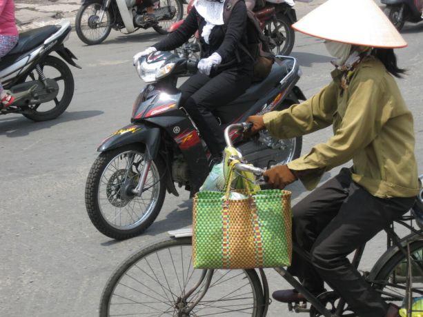 Vietnam: Woman on bike wearing conical hat, Vietnam More Info