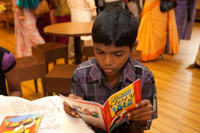 India: Kochi, India :: A local boy reads the Most Important Story Ever Told book. More Info