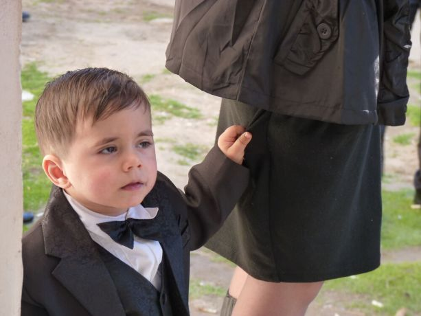 Caucasus: A young boy tagging along by tugging his mothers skirt on the way to an engagement party More Info