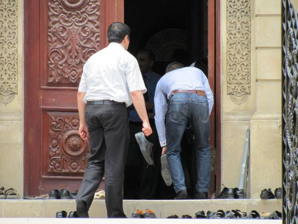 Caucasus: Two men removing their shoes before entering a mosque More Info